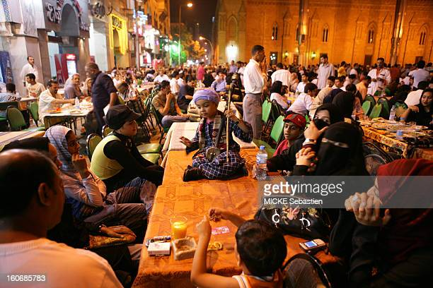 Front of the mosque of AlHoucine Sidna in Old Cairo families flock to outdoor cafes Here a young musician made his number for a few dollars