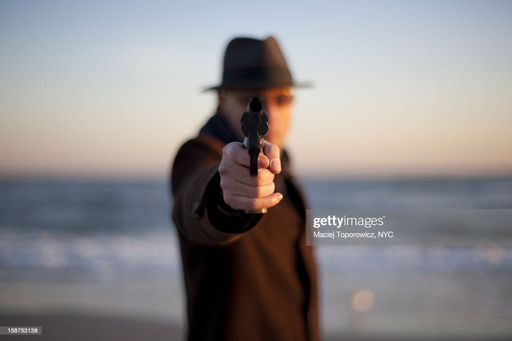 Front portrait of man aiming gun : Stock Photo