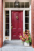 An inviting exterior with a front red door that is secured. The entryway is filled with a potted plant.