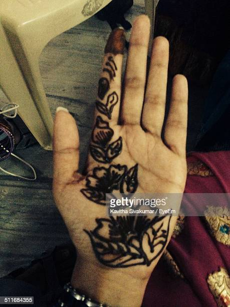 Front view image of a human palm with tattoo