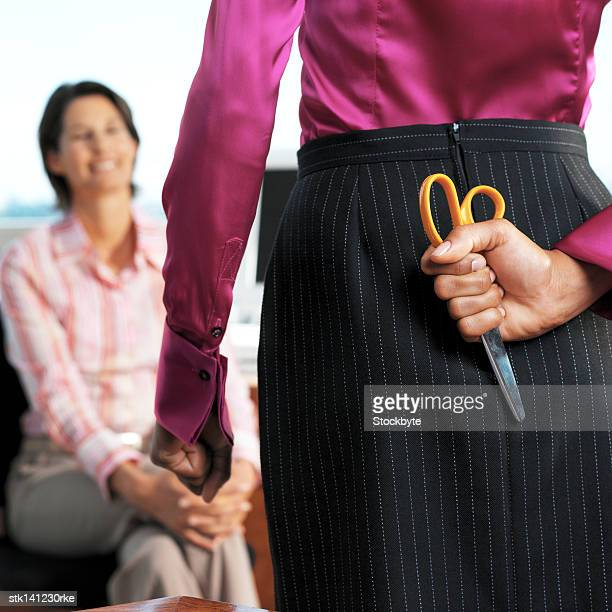 front view of a businesswoman and a rear view businesswoman standing holding a scissors behind her back