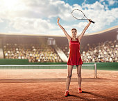 front view of a female tennis player on court  holding a tennis racket above her head and celebrating victory