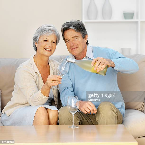 Front view of a mature couple sitting on sofa with man pouring wine into wineglass