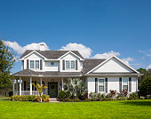 Traditional American home with space for copy; blue sky, extensive front lawn.