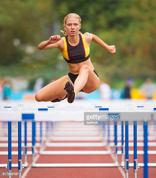 Front View of Beuatiful Young Women Racing 100m Hurdles