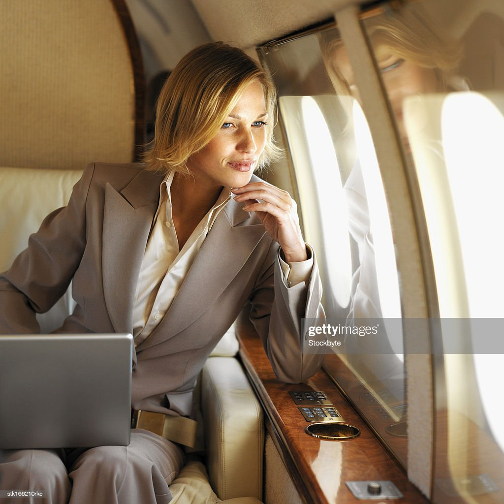 front view of businesswoman sitting holding laptop on her lap looking out window in first class airplane : Stock Photo