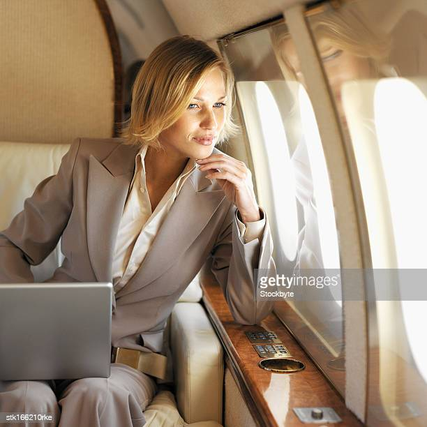 front view of businesswoman sitting holding laptop on her lap looking out window in first class airplane