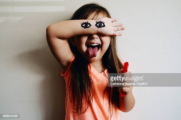 Front View Of Cute Girl Hand With Eyes Drawing Against White Wall