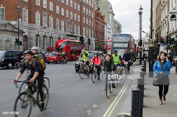 Front view of Cyclists, cars and buses riding on street