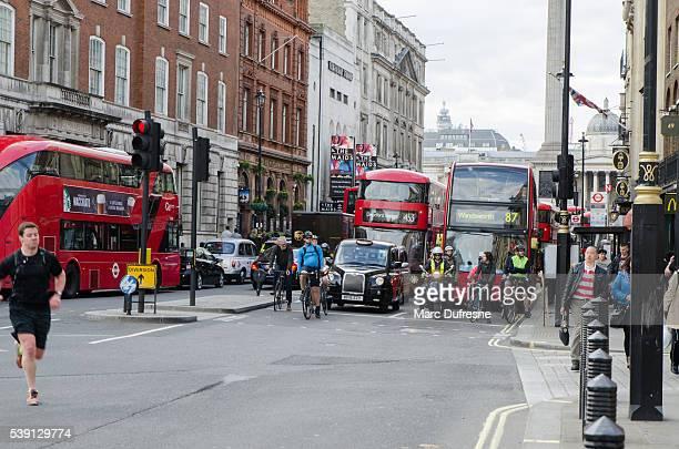 Frente vista de los ciclistas, autobuses y coches que espera