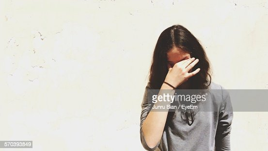 Front View Of Displeased Young Woman Against White Wall