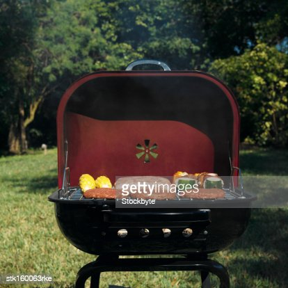 front view of hamburgers sausage corn and kebabs on barbeque : Stock Photo