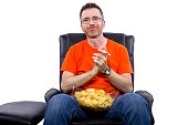 Front view of man watching TV while eating potato chips.  He is isolated on a white background.  The man is eating junk food and sitting down.  The man is realxing and perhaps on his day off. The imag