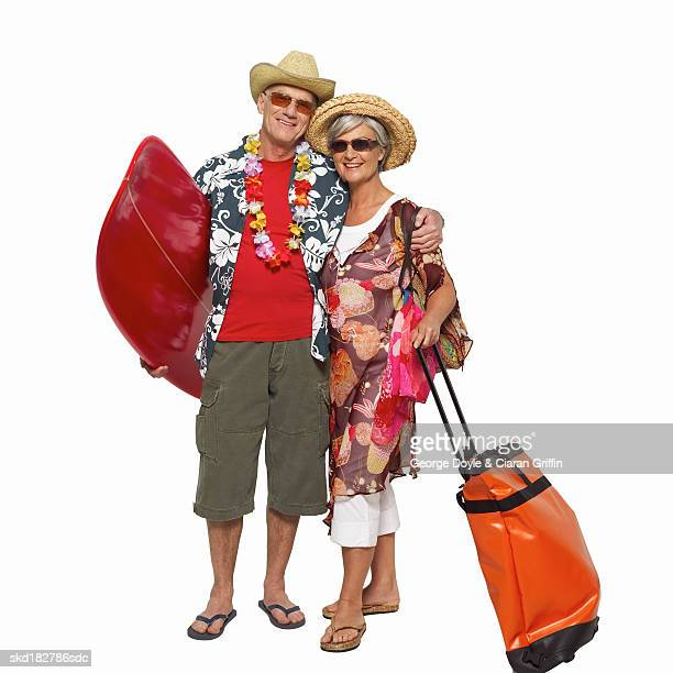 Front view of mature couple holding surfboard and bag