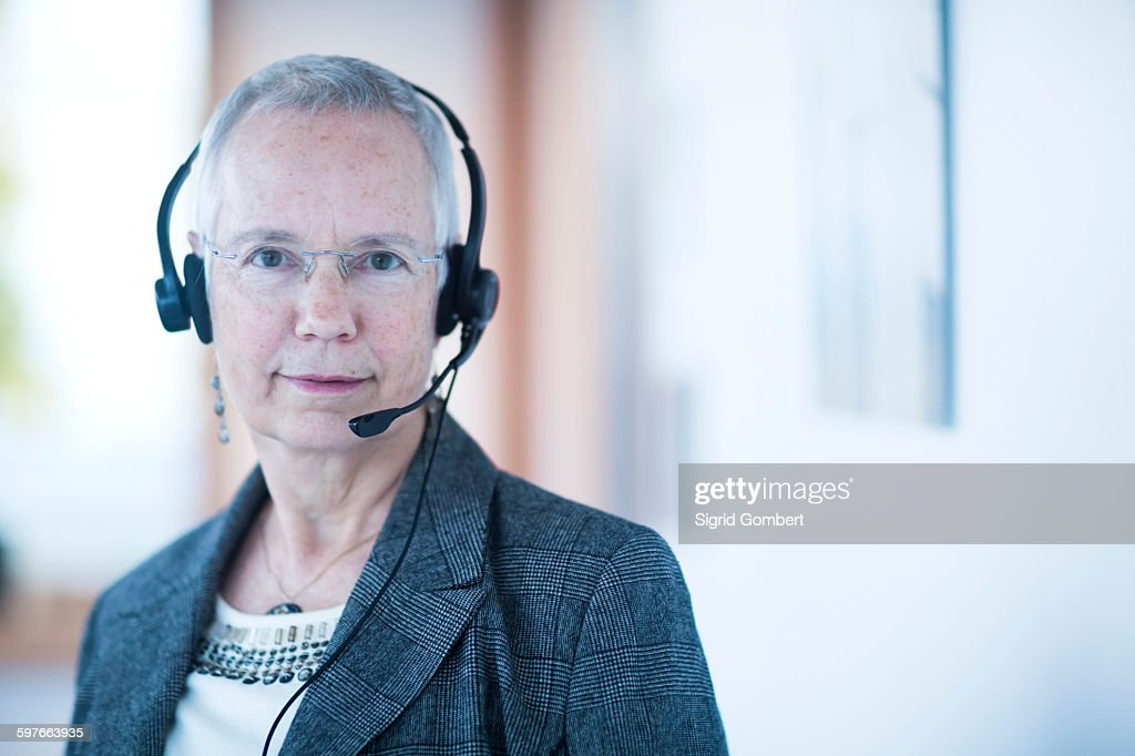 Front view of mature woman wearing telephone headset looking at camera