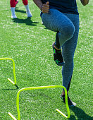 A high school female athlete performs running drills over mini hurdles while wearing socks but no shoes on a green turf field.