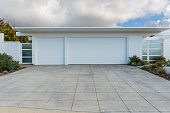 front view of white three car garage door with a long driveway, partly cloudy sky. the house is a mid-century modern style house