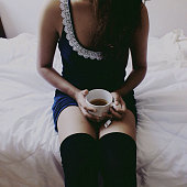 Front View Of Woman Sitting On Bed, Holding Mug