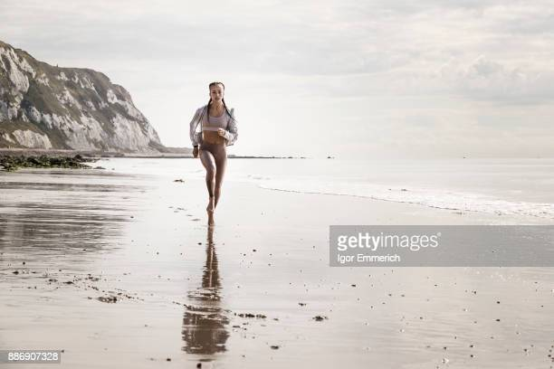 Front view of young female runner running barefoot along beach
