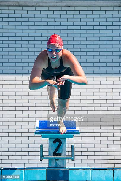 Front View of Young Female Swimmer Starting the Race