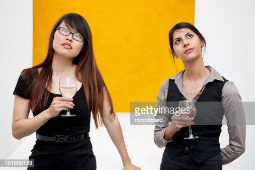Front view of young females with wine glass looking up in art gallery