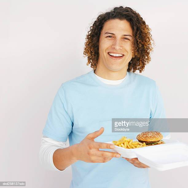 Front view of young man holding carton of French fries and burger