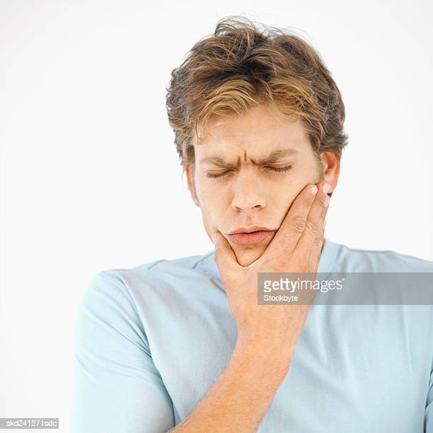 Front view of young man holding his cheek in pain