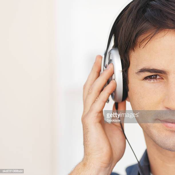 Front view of young man listening to music with headphones