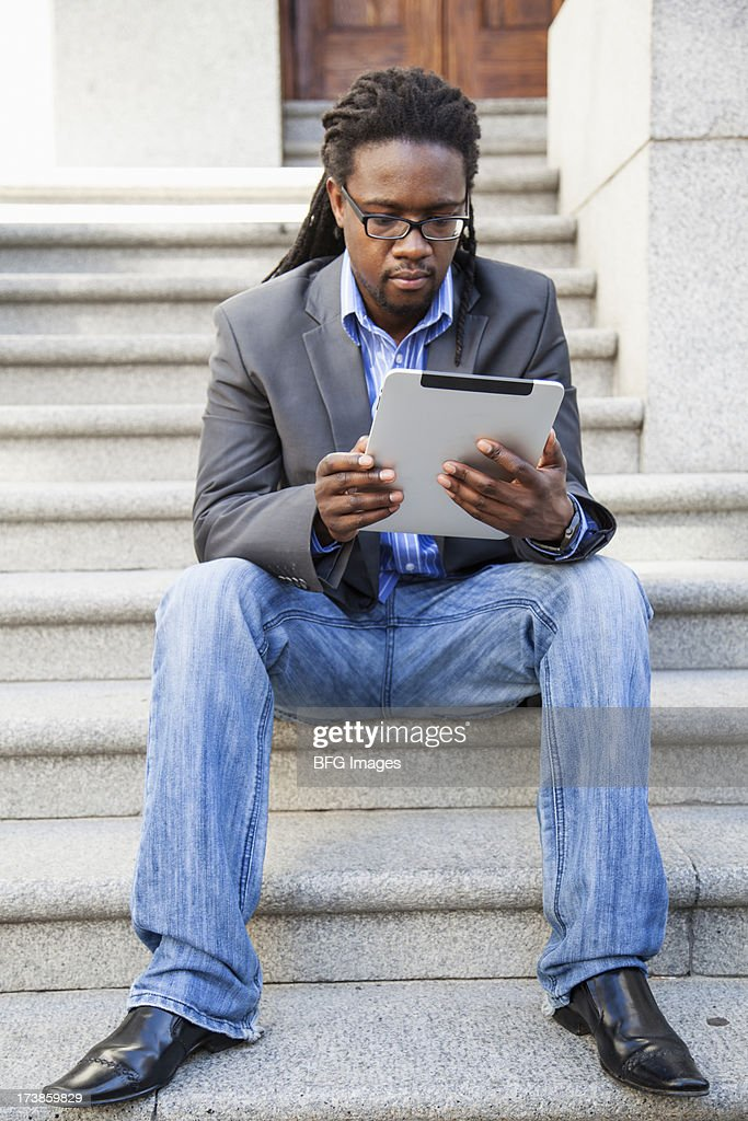 Front view of young man sitting on steps looking at his digital tablet. Cape Town, Western Cape Province, South Africa : Stock Photo