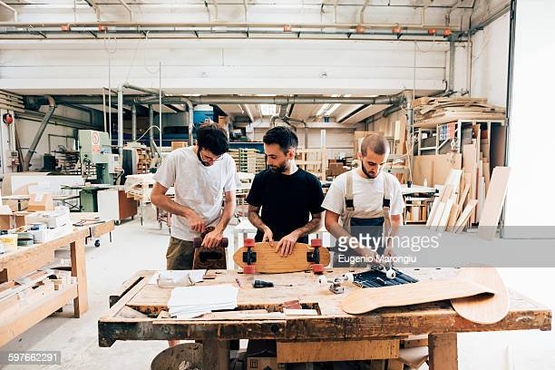 Front view of young men in carpentry workshop standing at workbench attaching wheels to skateboard