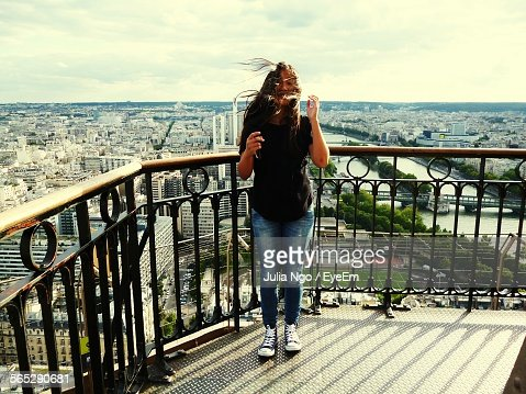 Front View Of Young Tourist Woman Against Railing Of Observation Point At Eiffel Tower