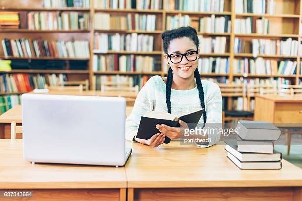 Front view of young woman reading a book at library