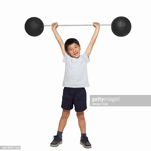 front view portrait of a boy (10-11) holding a dumbbell