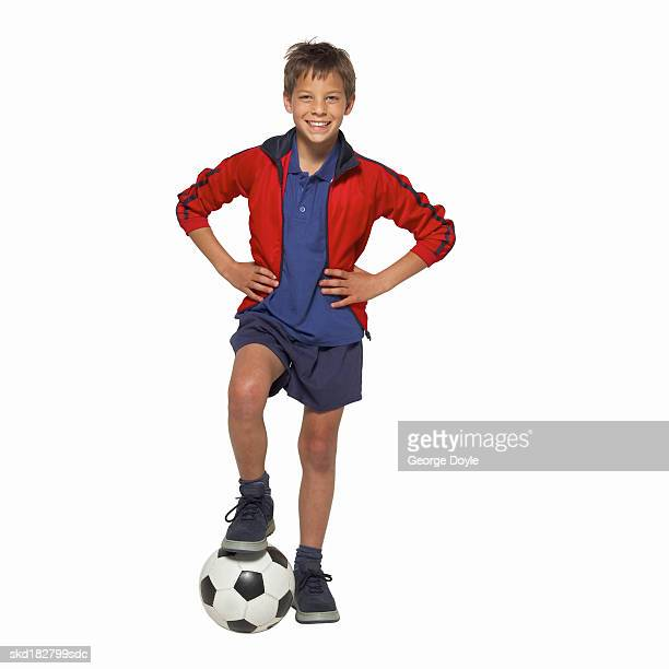 front view portrait of a boy (11-12) holding a soccer-ball with his leg