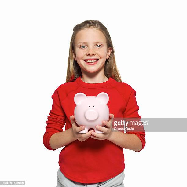 front view portrait of a girl (11-12) holding piggy bank