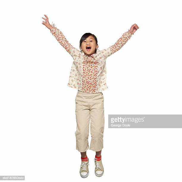 front view portrait of a girl (10-11) jumping on trampoline
