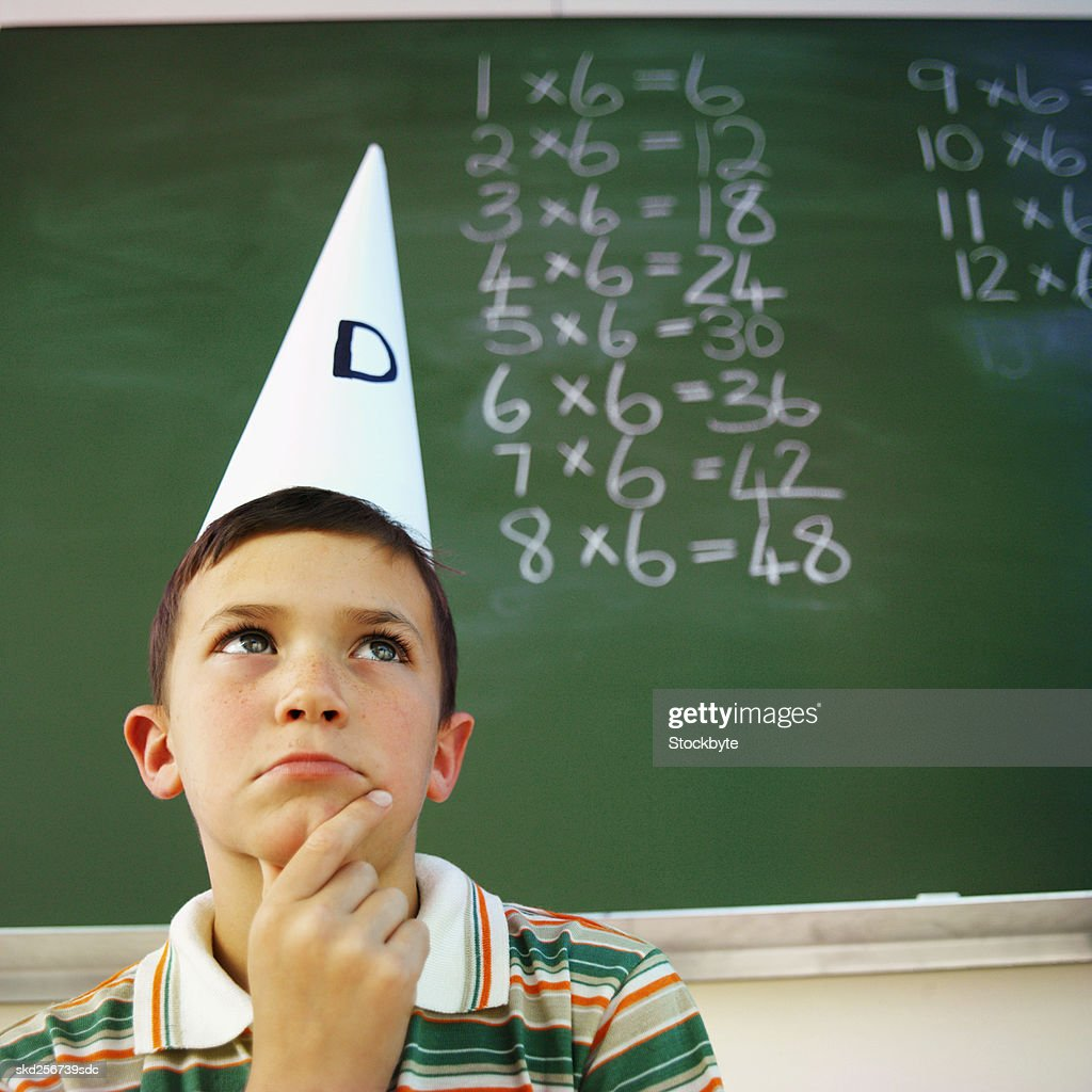 Front view portrait of boy wearing dunce cap (10-11)