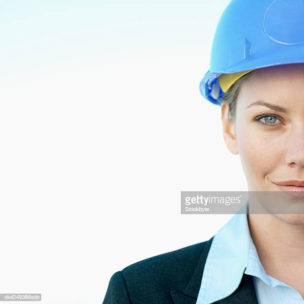 Front view portrait of businesswoman smiling and wearing hard hat