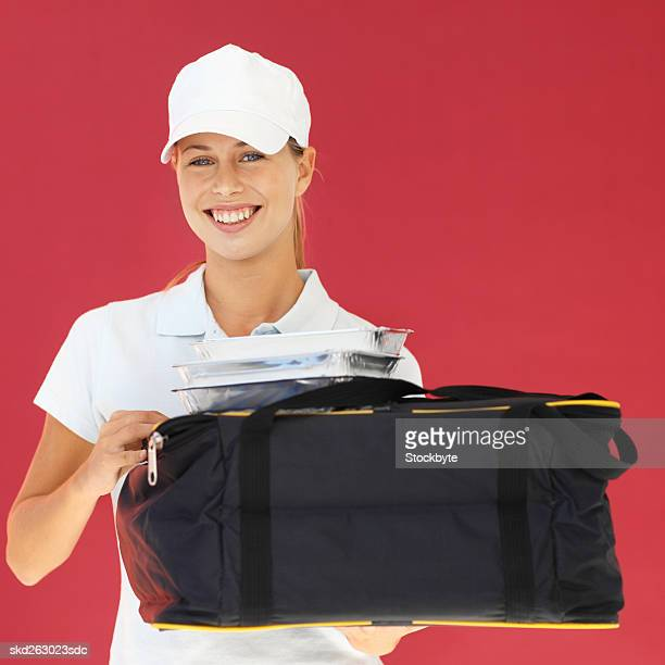 Front view portrait of delivery woman holding fast-food