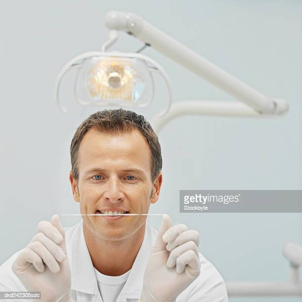 Front view portrait of dentist holding dental floss