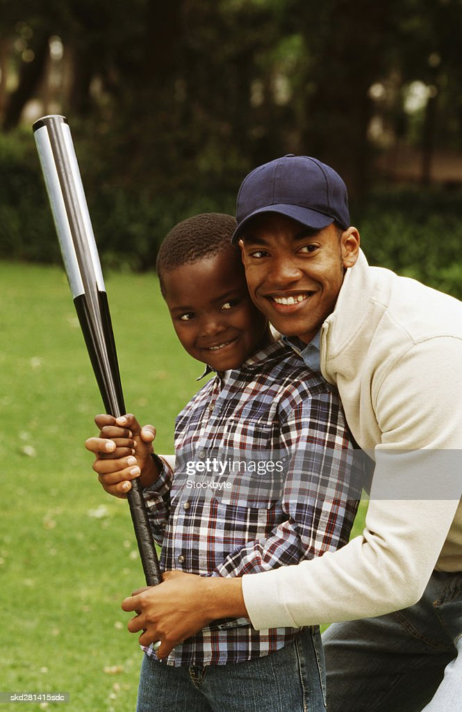 Front view portrait of father and son playing baseball (10-11)