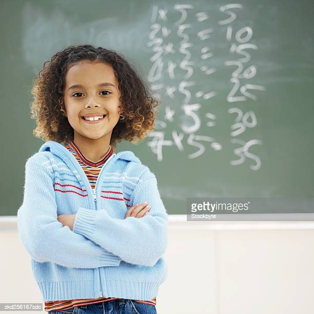 Front view portrait of girl standing in front of chalkboard with arms crossed (8-9)