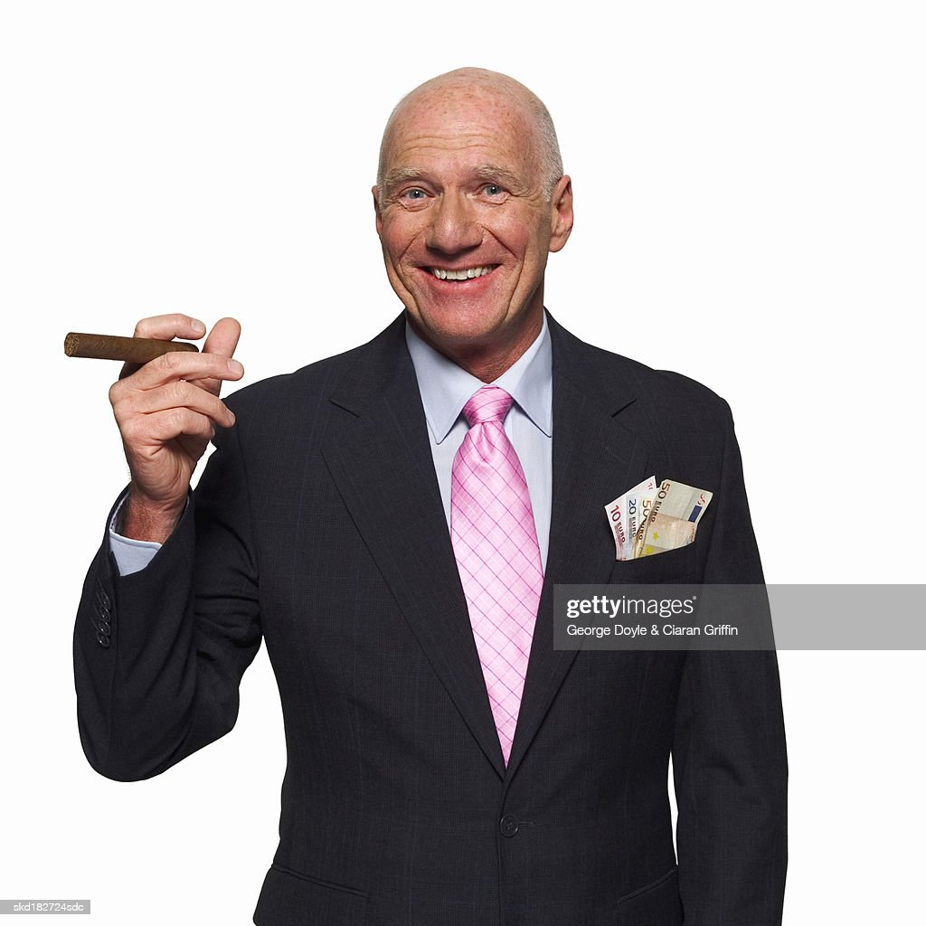 Front view portrait of mature businessman holding cigar : Stock Photo