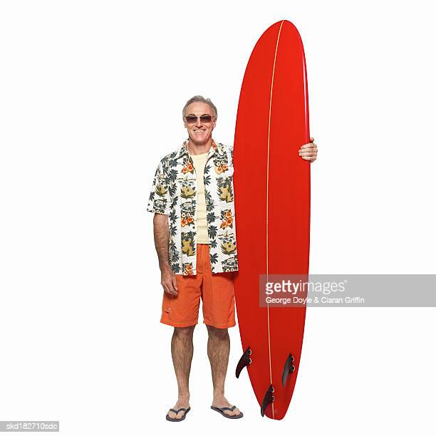 Front view portrait of mature man holding surfboard