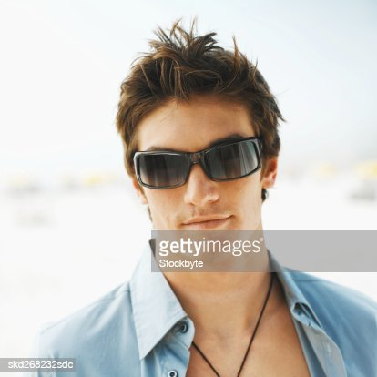 Front view portrait of young man smiling and wearing sunglasses : Stock Photo