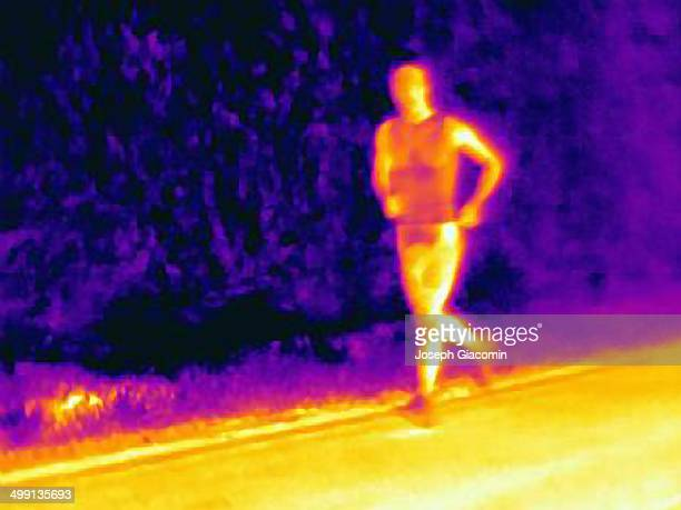 Front view thermal photograph of young male athlete running. The image shows the heat of the muscles