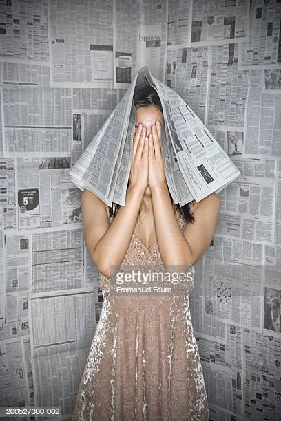 Front view, young woman covered by newspaper, hands covering face