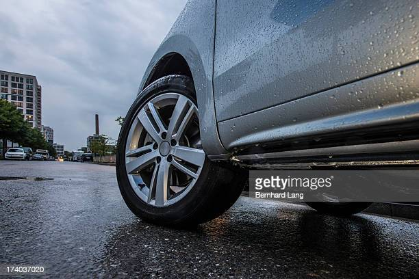Front wheels of a car on urban street, low angle