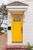 Beach house with bright yellow front door with white siding and brick stairs.