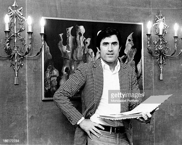 Frontal portrait of the Italian actor Lando Buzzanca wearing a pied de poule pattern jacket and pair of jeans and standing in front of two wall lamps...